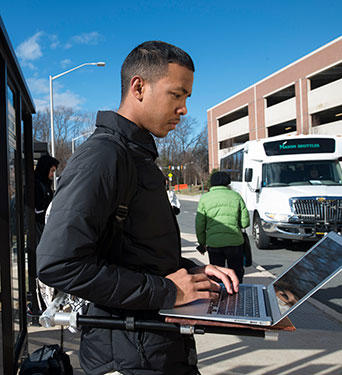 Volgenau mechanical engineering major, Marqus Keith, tries out a prototype of his invention at a bus stop on campus.